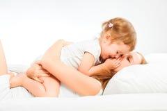 Den lyckliga familjmodern och behandla som ett barn dottern som spelar, och skratta behandla som ett barn Fotografering för Bildbyråer
