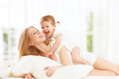 Den lyckliga familjmodern och behandla som ett barn dottern som spelar, och skratta behandla som ett barn Arkivbild