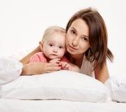 Den lyckliga familjmodern och behandla som ett barn ha gyckel på säng royaltyfri foto