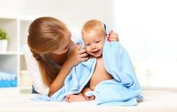 Den lyckliga familjmodern och behandla som ett barn i en blå handduk, når han har badat Fotografering för Bildbyråer