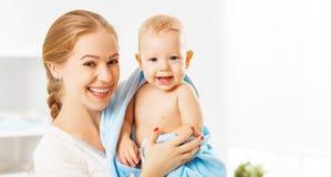 Den lyckliga familjmodern och behandla som ett barn i en blå handduk, når han har badat Arkivbild