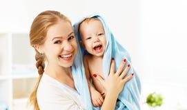 Den lyckliga familjmodern och behandla som ett barn i en blå handduk, når han har badat Royaltyfri Bild