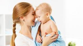 Den lyckliga familjmodern och behandla som ett barn i en blå handduk, når han har badat Arkivbilder