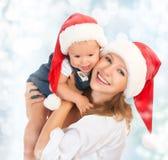 Den lyckliga familjmodern och behandla som ett barn i julhattar Arkivbild