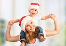 Den lyckliga familjmodern och behandla som ett barn i julhattar Fotografering för Bildbyråer