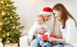 Den lyckliga familjmodern och behandla som ett barn i julmorgon på jul t Arkivfoton