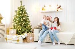 Den lyckliga familjmodern och behandla som ett barn i julmorgon på jul t Royaltyfria Bilder