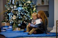 Den lyckliga familjmodern och behandla som ett barn den lilla sonen som hem spelar på julferier Ferier för ` s för nytt år royaltyfri bild