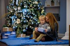 Den lyckliga familjmodern och behandla som ett barn den lilla sonen som hem spelar på julferier Ferier för ` s för nytt år royaltyfri foto
