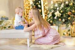 Den lyckliga familjmodern och behandla som ett barn den lilla sonen som hem spelar på julferier Litet barn med mamman i det festi Fotografering för Bildbyråer