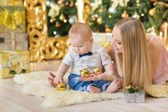 Den lyckliga familjmodern och behandla som ett barn den lilla sonen som hem spelar på julferier Litet barn med mamman i det festi Arkivfoto