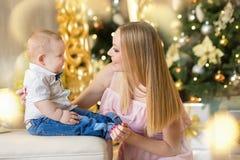 Den lyckliga familjmodern och behandla som ett barn den lilla sonen som hem spelar på julferier Litet barn med mamman i det festi Arkivfoton