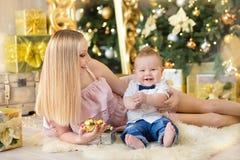 Den lyckliga familjmodern och behandla som ett barn den lilla sonen som hem spelar på julferier Litet barn med mamman i det festi Royaltyfri Bild