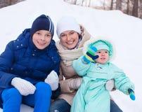 Den lyckliga familjmodern och behandla som ett barn, och tonåringen i vinter parkerar Arkivfoton