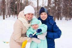 Den lyckliga familjmodern och behandla som ett barn, och tonåringen i vinter parkerar Royaltyfri Fotografi