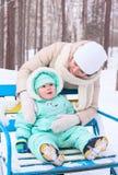 Den lyckliga familjmodern och behandla som ett barn parkerar in i vinter Royaltyfri Fotografi