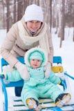 Den lyckliga familjmodern och behandla som ett barn parkerar in i vinter Arkivfoton
