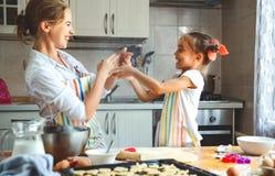 Den lyckliga den familjmodern och dottern bakar att knåda deg i kök arkivbilder