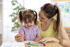 Den lyckliga den familjmodern och dottern målar tillsammans Kvinnan hjälper barnflickan Arkivbild