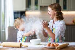 Den lyckliga den familjmodern och sonen bakar att knåda deg i kök royaltyfria foton