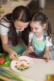 Den lyckliga familjmodern och ungeflickan förbereder sund mat, dem improviserar tillsammans i köket Royaltyfri Fotografi