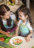 Den lyckliga familjmodern och ungeflickan förbereder sund mat, dem improviserar tillsammans i köket Royaltyfri Foto