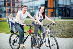 Den lyckliga familjridningen cyklar i staden arkivbild