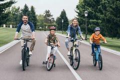 Den lyckliga familjridningen cyklar och spendera tid tillsammans arkivbild
