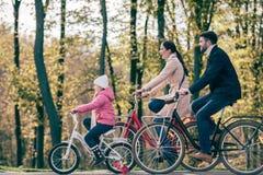 Den lyckliga familjridningen cyklar parkerar in Arkivfoto