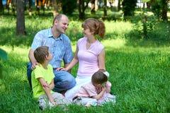 Den lyckliga familjståenden på utomhus-, gruppen av fem personer sitter på gräs i stad parkerar, sommarsäsongen, barnet och föräl Royaltyfria Bilder