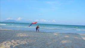 Den lyckliga farmodern med barnet den spela flygadraken, familjen kör på sanden av ett tropiskt hav som spelar med lager videofilmer