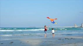 Den lyckliga farmodern med barnet den spela flygadraken, familjen kör på sanden av ett tropiskt hav som spelar med arkivfilmer
