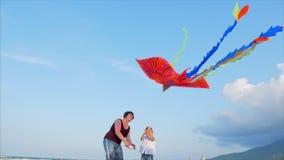 Den lyckliga farmodern med barnet den spela flygadraken, familjen kör på sanden av ett tropiskt hav som spelar med stock video
