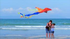 Den lyckliga farmodern med barnet den spela flygadraken, familjen k?r p? sanden av ett tropiskt hav som spelar med lager videofilmer
