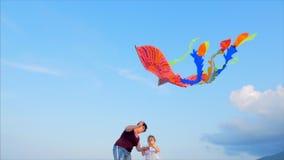 Den lyckliga farmodern med barnet den spela flygadraken, familjen k?r p? sanden av ett tropiskt hav som spelar med arkivfilmer