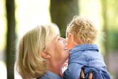 Den lyckliga farmodern som kramar behandla som ett barn lite, flickan Arkivfoto