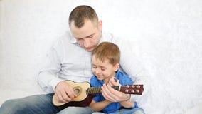 Den lyckliga farsan undervisar hans son att spela gitarren på en vit soffa Begreppet av en lycklig familj stock video