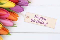 Den lyckliga födelsedagen med tulpan blommar på träbräde Fotografering för Bildbyråer