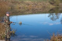 Den lyckliga fiskaren fångar en fisk royaltyfria foton