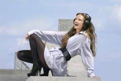 Den lyckliga flickan är lyssnande musik Arkivbilder