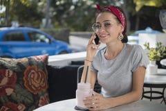 Den lyckliga flickan är på mobiltelefonen som sitter i gatakafét, modell poserar med telefonen royaltyfria bilder