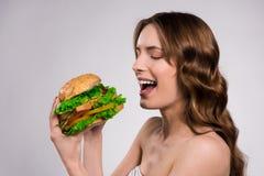 Den lyckliga flickan äter den isolerade hamburgaren arkivbild