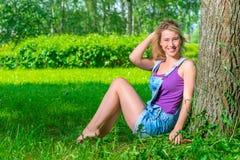 Den lyckliga flickan 20 år sitter nära trädet Royaltyfri Bild