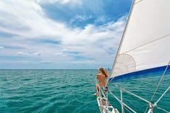 Den lyckliga flickan av seglingyachten har ombord en gyckel arkivfoto