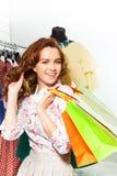 Den lyckliga flickan bär shoppingpåsar i galleria Arkivfoton