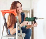 Den lyckliga flickan borrar hålet i väggen Royaltyfria Bilder