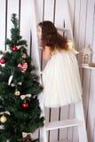 Den lyckliga flickan dekorerar julgranen. Arkivbild