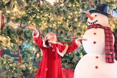 Den lyckliga flickan för det lilla barnet i santa dräktklänning har gyckel och lek med snö på vintertid mot julbakgrund Glade Chr royaltyfri foto