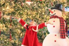 Den lyckliga flickan för det lilla barnet i santa dräktklänning har gyckel och lek med snö på vintertid mot julbakgrund glatt royaltyfria foton
