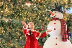 Den lyckliga flickan för det lilla barnet i santa dräktklänning har gyckel och lek med snö på vintertid mot julbakgrund glatt fotografering för bildbyråer